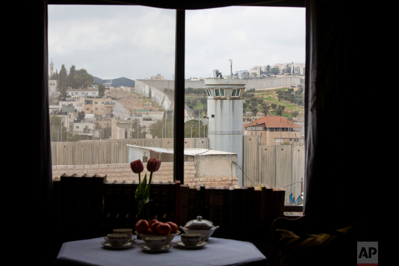 "An Israeli security watch tower is seen from one of the rooms of the ""The Walled Off Hotel"" in the West Bank city of Bethlehem, Friday, March 3, 2017. The owner of a guest house packed with the elusive artist Banksy's work has opened the doors of his West Bank establishments to media, showcasing its unique ""worst view in the world."" The nine-room hotel named ""The Walled Off Hotel"" will officially open on March 11. (AP Photo/Dusan Vranic)"