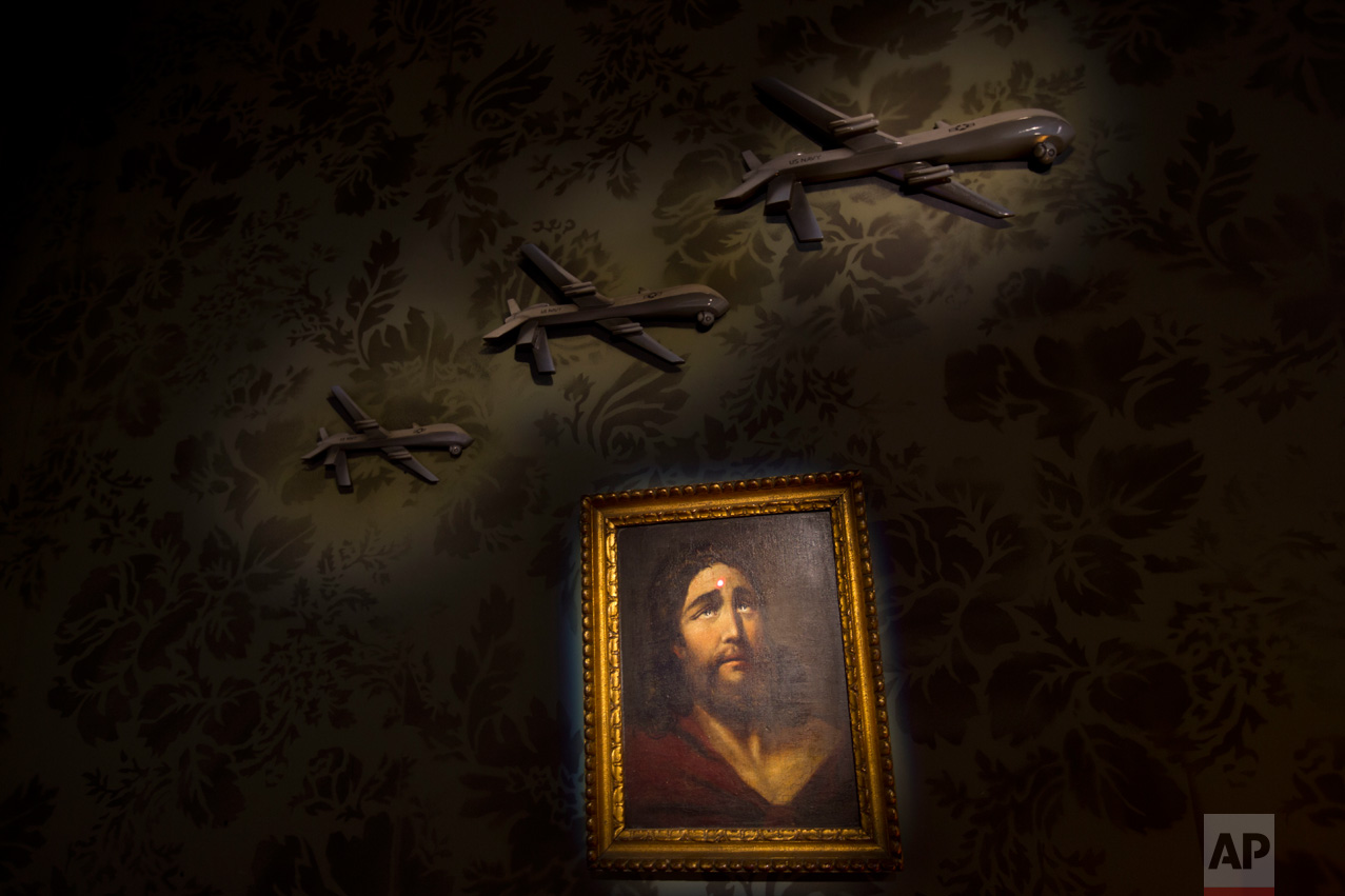 "A wall decorated with models of drones and a painting of Jesus with a sniper's dot on his forehead is seen in the ""The Walled Off Hotel"" in the West Bank city of Bethlehem, Friday, March 3, 2017. The owner of a guest house packed with the elusive artist Banksy's work has opened the doors of his West Bank establishments to media, showcasing its unique ""worst view in the world."" The nine-room hotel named ""The Walled Off Hotel"" will officially open on March 11. (AP Photo/Dusan Vranic)"