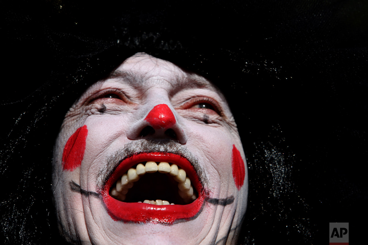 "A clown-faced reveler smiles as he takes part in the ""Galo da Madrugada"" or the Morning Rooster carnival parade, in downtown Recife, in the Brazilian state of Pernambuco, Saturday, Feb. 25, 2017. The ""Galo da Madrugada"" took to the streets for the first time in 1975 with the aim of rescuing the traditional carnival of Recife. It is now considered one of the largest carnival parades. (AP Photo/Eraldo Peres)"