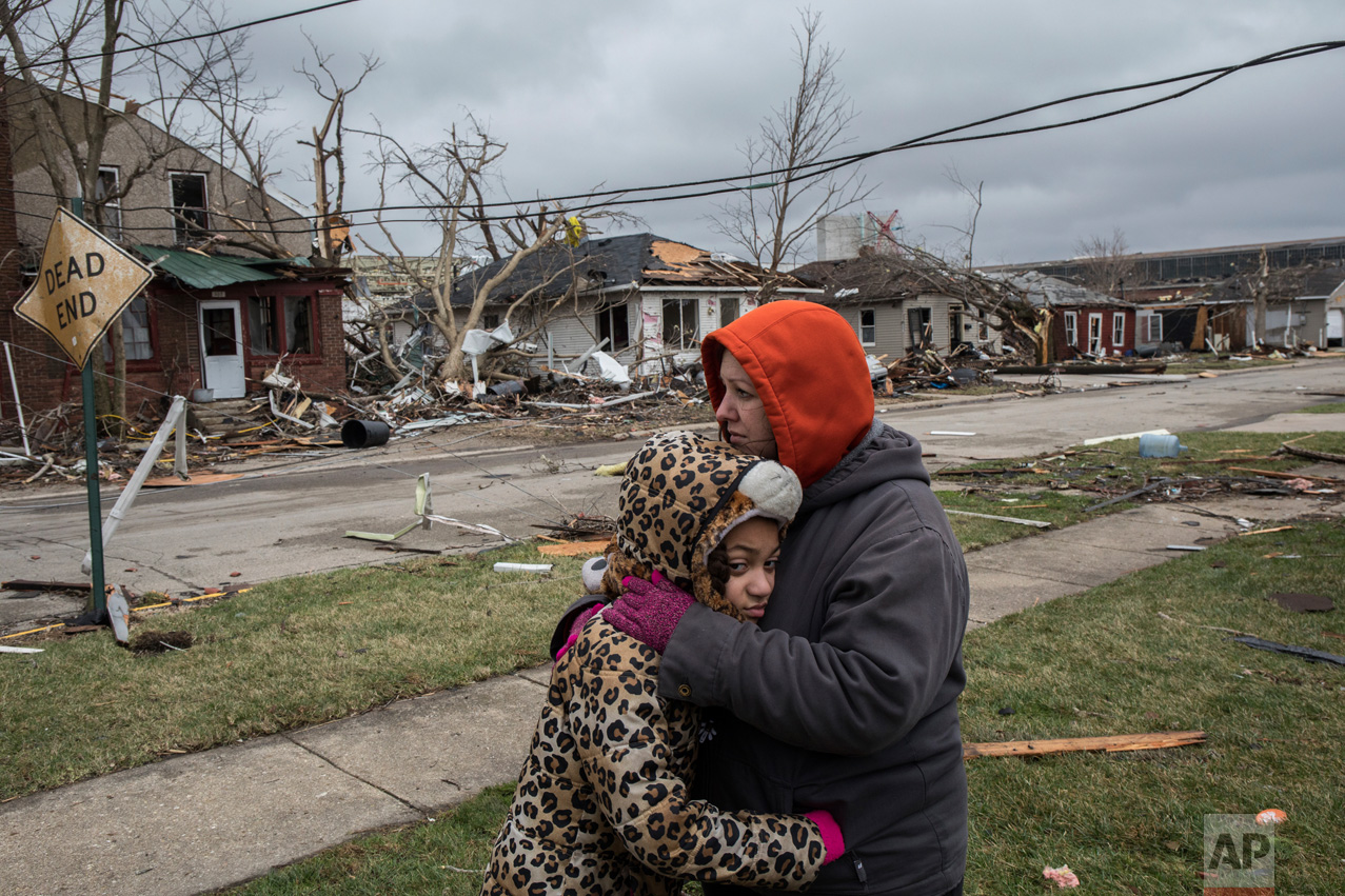 Residents Valerie McAvoy hugs her daughter, Jayda Weathersby, 9, as they survey tornado damage to their neighborhood in Naplate, Ill., on Wednesday, March 1, 2017. Deadly storms producing tornadoes moved through areas of the Midwest. (Zbigniew Bzdak/Chicago Tribune via AP)