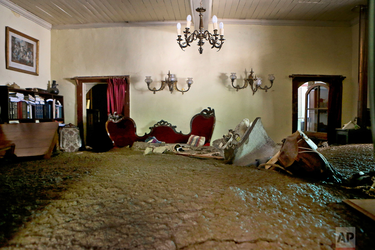 Sludge from the overflowing of the Estero San Jose River fills the living room of a home in San Alfonso, Santiago, Chile, Sunday, Feb. 26, 2017. Floods caused by Andean rainfall are causing havoc in parts of Chile, triggering landslides, cutting roads and isolating thousands of people. (AP Photo/Esteban Felix)