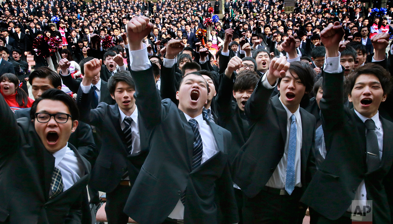College students raise clenched fists during a joint pep rally to launch their job-hunting at Tokyo's Hibiya park Wednesday, March 1, 2017. (AP Photo/Shizuo Kambayashi)