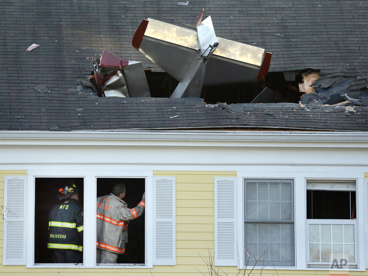 Firefighters investigate the site of a single-engine aircraft collision into a building across the Merrimack River from Lawrence Municipal Airport in Methuen, Mass., on Tuesday, Feb. 28, 2017. According to police, the pilot of the home-built plane was killed, while no one in the building was hurt. (AP Photo/Elise Amendola)