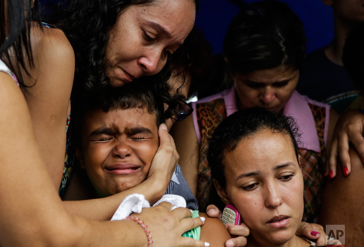 Kailua, center, son of slain civil police officer Mario Marcelo de Albuquerque Espirito, is comforted during his father's funeral, alongside his mother Patricia Albuquerque, right, in Serra, Espirito Santo state, Brazil, Wednesday, Feb 8, 2017. Mario Marcelo de Albuquerque was shot to death when he tried to impede a robbery. (AP Photo/Diego Herculano)