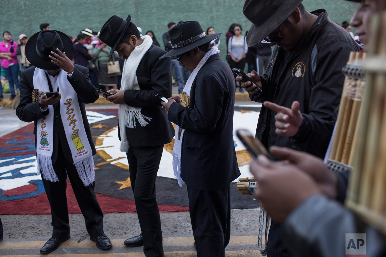 Musicians check their cell phones during a pause in the procession celebrating the feast day of the Virgin of Candelaria, in Puno, Peru, Thursday, Feb. 2, 2017. (AP Photo/Rodrigo Abd)
