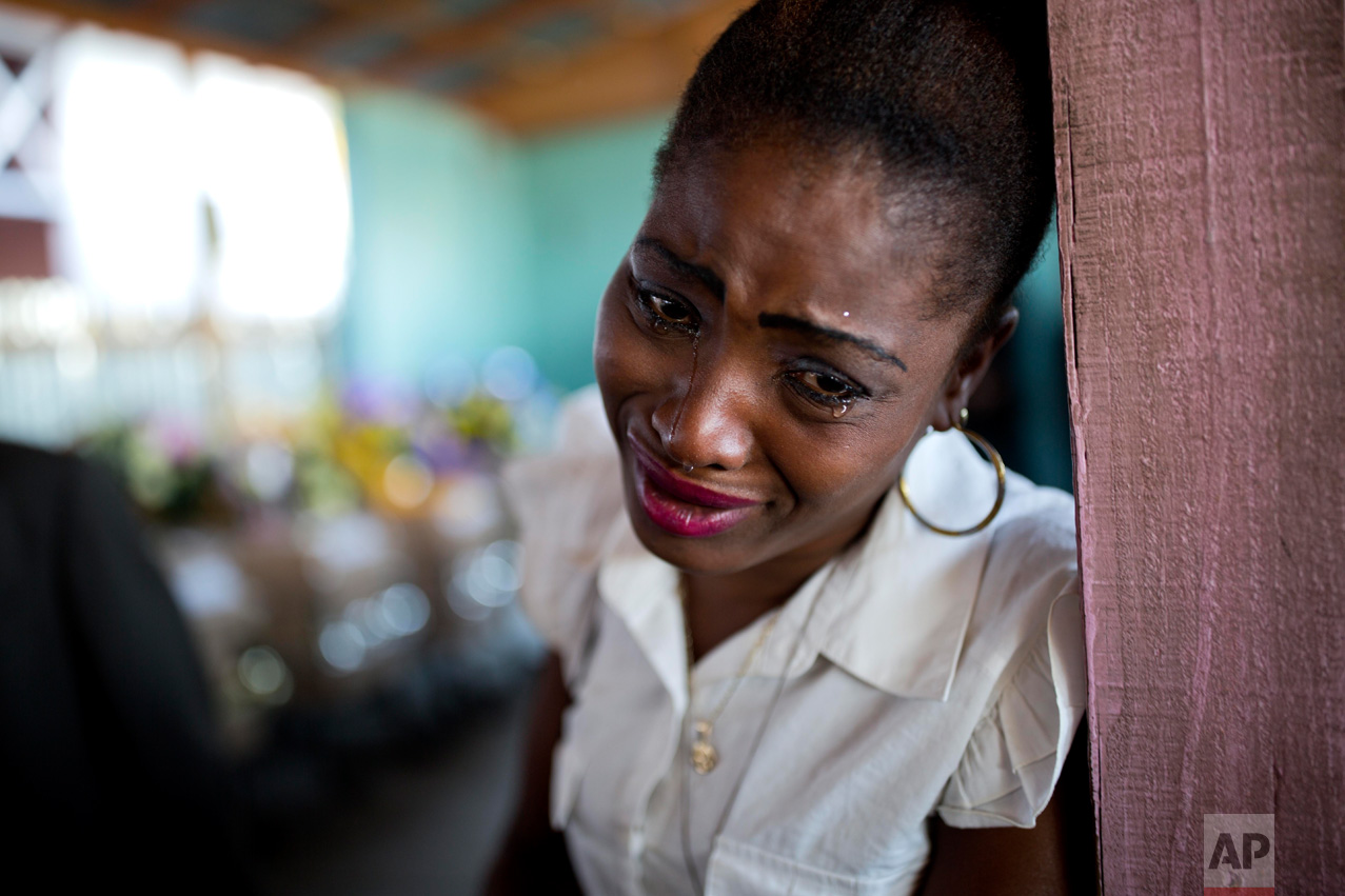 A woman cries near the coffin containing the body of a relative who died at the country's largest prison in Port-au-Prince, Haiti, Tuesday Feb. 21, 2017. Relatives wailed in grief or stared stoically as flowers were placed on 20 caskets at a mass funeral for the latest group of inmates who died miserably in Haiti's largest prison, most without ever having been convicted of any crime. (AP Photo/Dieu Nalio Chery)