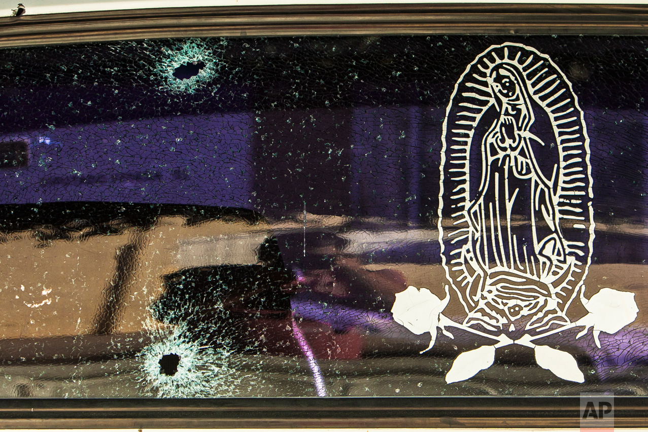 The rear windshield of a vehicle is held together by a transparent film with an image of the Virgin of Guadalupe, after being struck by a couple of bullets in Culiacan, Mexico, Tuesday, Feb. 7, 2017. The Sinaloa state prosecutor's office said in a statement that several suspects and a Mexican marine died in an early morning clash after heavily armed men attacked the marines while on patrol in the city. (AP Photo/Rashide Frias)