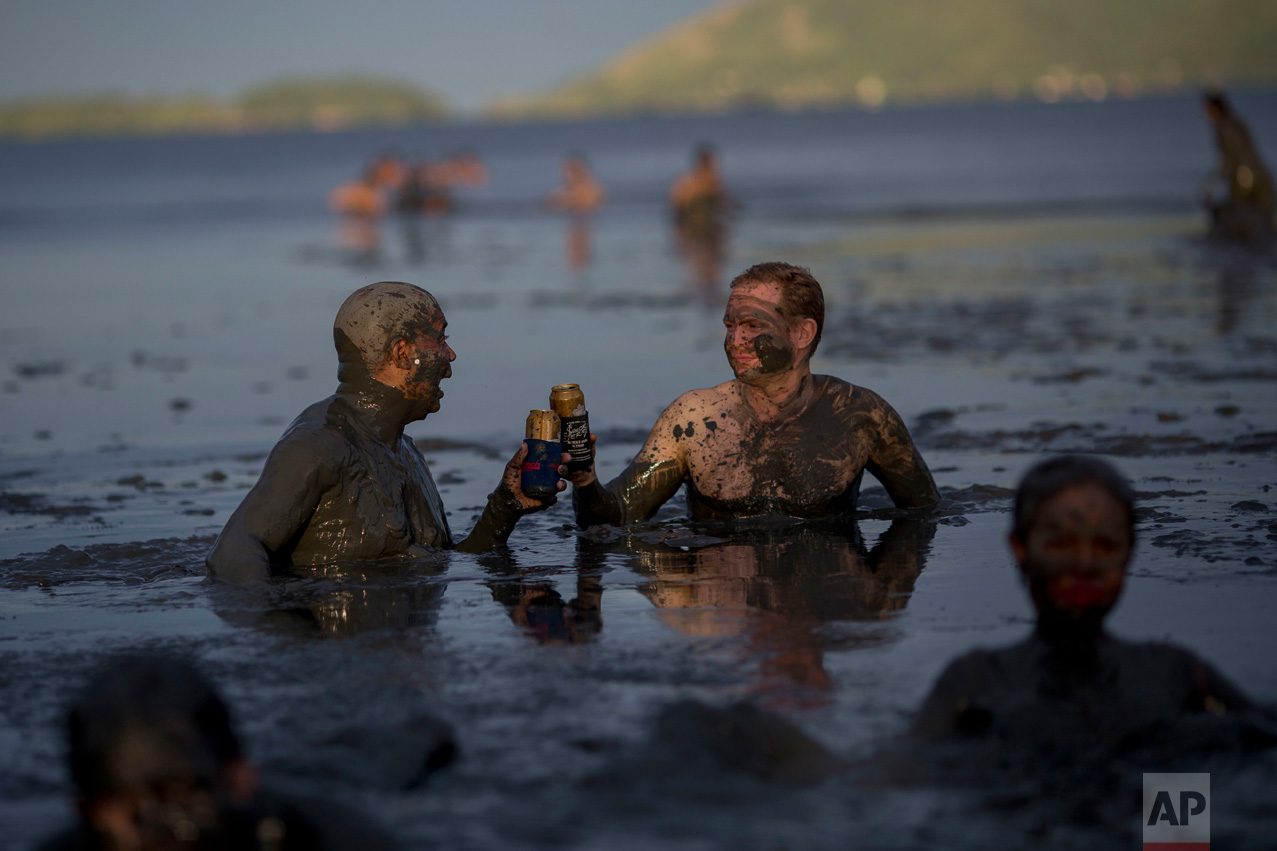 "Two men toast beer while wading in mud during the traditional ""Bloco da Lama"" or ""Mud Street"" carnival party, in Paraty, Brazil, Saturday, Feb. 25, 2017. Legend has it the ""bloco"" was born in 1986 after local teens hiking in a nearby mangrove forest smeared themselves with mud to discourage mosquitoes and then wandered through Paraty. The party grew year after year, but revelers eventually were banned from parading in the colonial downtown after shopkeepers complained pristine white walls were stained with the hard-to-remove mud. (AP Photo/Mauro Pimentel)"