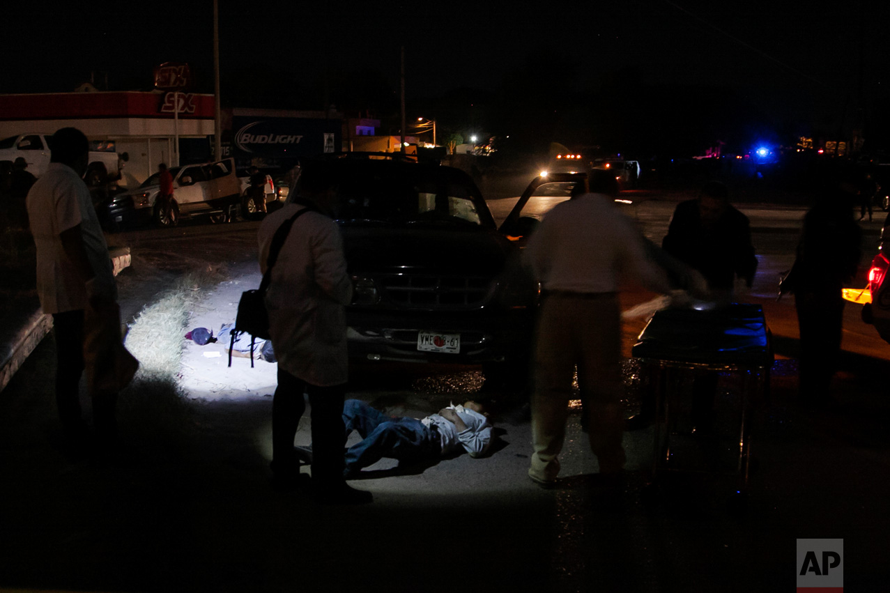 Forensic medics investigate a crime scene where two people were shot dead by unidentified attackers in Culiacan, Mexico, late Tuesday, Feb. 7, 2017. More people have been killed in Sinaloa state, hours after several suspects and a marine died during a clash in the city. (AP Photo/Rashide Frias)