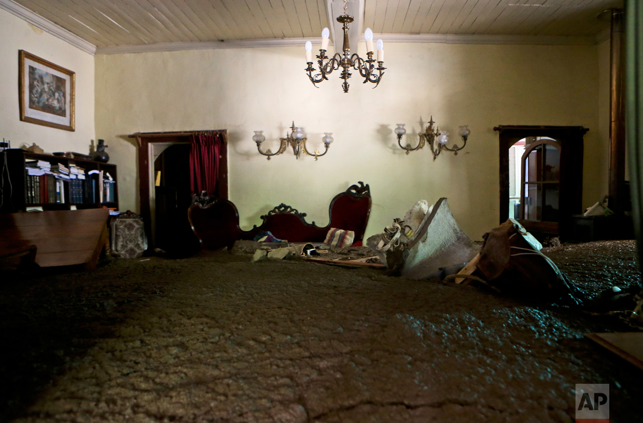 Sludge fills the living room of a home, brought by the overflowing of the Estero San Jose River in San Alfonso, Santiago, Chile, Sunday, Feb. 26, 2017. Floods caused by Andean rainfall are causing havoc in parts of Chile, triggering landslides, cutting roads and isolating thousands of people. (AP Photo/Esteban Felix)