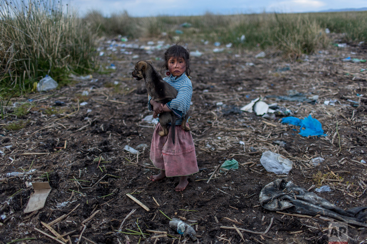 In this Feb. 4, 2017 photo, Melinda Quispe walks on the trash strewn shore of Lake Titicaca, as she holds her dog, in her village Kapi Cruz Grande, in the Puno region of Peru. The governments of Peru and Bolivia signed a pact in January to spend more than $500 million to attack the pollution problem of Lake Titicaca, though the details were vague. (AP Photo/Rodrigo Abd)