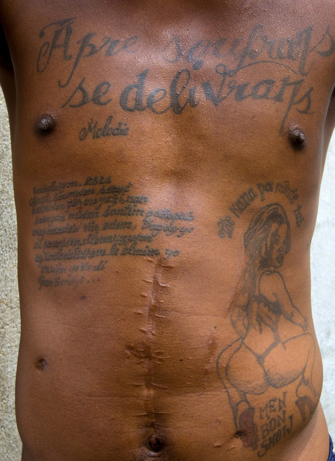 "This Feb. 13, 2017 photo shows the tattoos on the chest and abdomen of a prisoner incarcerated at the National Penitentiary in downtown Port-au-Prince, Haiti. The tattoo on his chest reads in Haitian Creole: ""After suffering is deliverance."" ( AP Photo/Dieu Nalio Chery)"