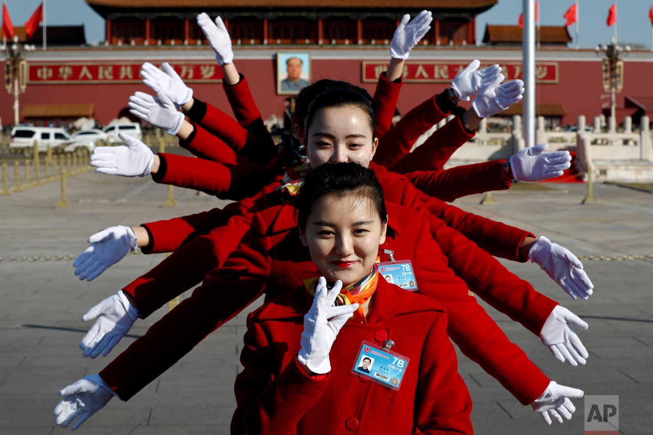 In this Sunday, March 5, 2017 photo, hospitality staff pose for photos on Tiananmen Square during the National People's Congress held at the Great Hall of the People in Beijing. (AP Photo/Andy Wong)
