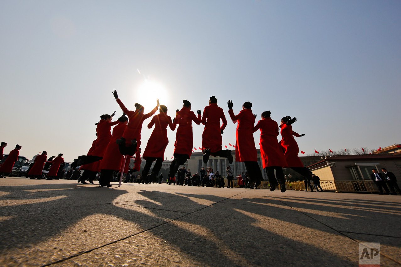 In this Friday, March 3, 2017 photo, hospitality staff jump as they pose for photographs on Tiananmen Square during the Chinese People's Political Consultative Conference (CPPCC) held at the Great Hall of the People in Beijing.(AP Photo/Andy Wong)