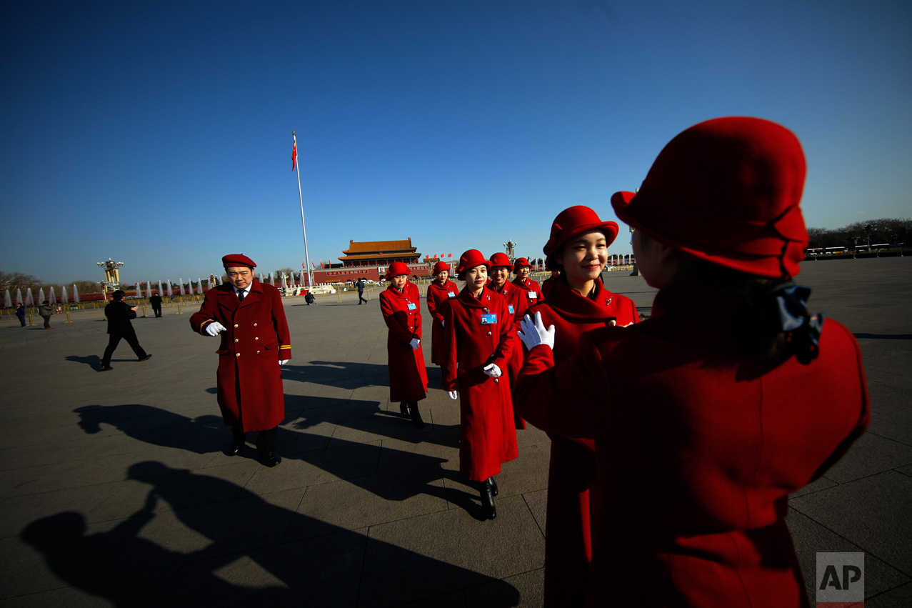 In this Sunday, March 5, 2017 photo, a hospitality staffer poses her colleagues for photographs on Tiananmen Square during the National People's Congress held at the Great Hall of the People in Beijing.(AP Photo/Andy Wong)
