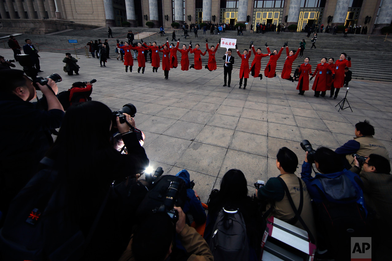 In this Friday, March 3, 2017 photo, hospitality staff jump as they pose for photographs in front of the Great Hall of the People during the Chinese People's Political Consultative Conference (CPPCC) in Beijing. (AP Photo/Andy Wong)