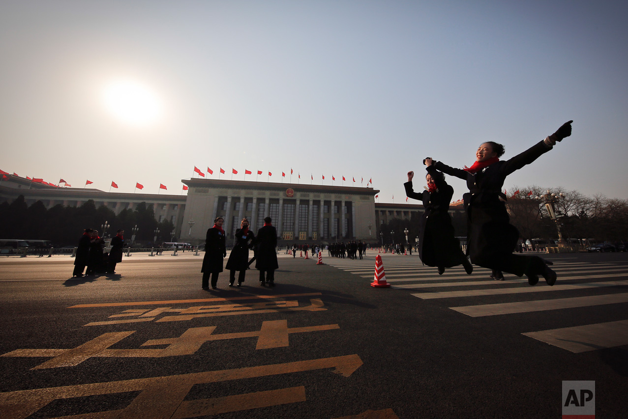 In this Friday, March 3, 2017 photo, hospitality staff jump as they pose for photographs on an empty street adjacent to the Great Hall of the People during the Chinese People's Political Consultative Conference (CPPCC) in Beijing. (AP Photo/Andy Wong)