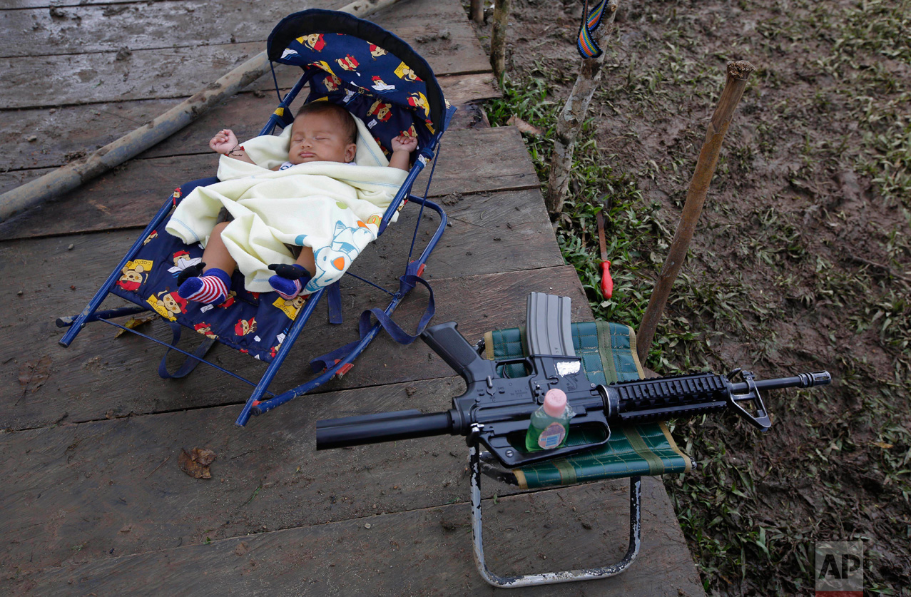 In this Tuesday, Feb. 28, 2017 photo, 3-month-old Junior Alexis Patino, son of FARC rebel Deisy Garcia, sleeps next to his mother's weapon at a rebel camp in a demobilization zone in La Carmelita, in Colombia's southwestern Putumayo state. Amid the makeshift tents and communal kitchens where Colombia's largest rebel army is preparing to lay down its weapons, a new sound is emerging: the cries of babies. (AP Photo/Fernando Vergara)