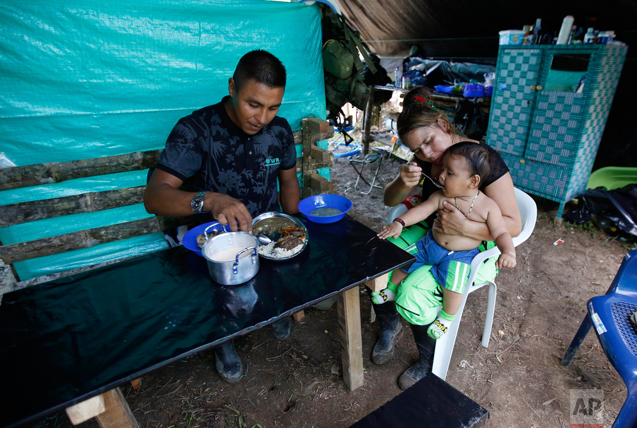 In this Tuesday, Feb. 28, 2017, rebel couple Jerly Suarez, right, and Vicente Pulecio eat lunch with their 9-month-old son Dainer inside their rebel camp tent within a demobilization zone in La Carmelita in Colombia's southwestern Putumayo state. As the guerrilla army is preparing to lay down its weapons, a rebel baby boom has struck a chord among urban Colombians far removed from the conflict, a few of whom have mobilized to transport diapers and creams to the new mothers after seeing images of sweltering infants on cots in the rural encampments. (AP Photo/Fernando Vergara)