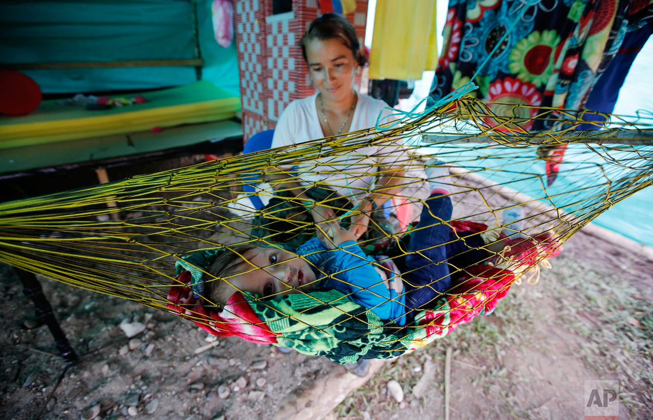 "In this Tuesday, Feb. 28, 2017 photo, FARC rebel Nelcy Rios cares for her 9-month-old daughter Naiha Sofia inside her tent at a rebel camp in a demobilization zone in La Carmelita, in Colombia's southwestern Putumayo state. Some of the guerrilla mothers are giving birth in camps, but most at nearby hospitals. Many in Colombia are referring to the babies as the ""children of peace."" (AP Photo/Fernando Vergara)"
