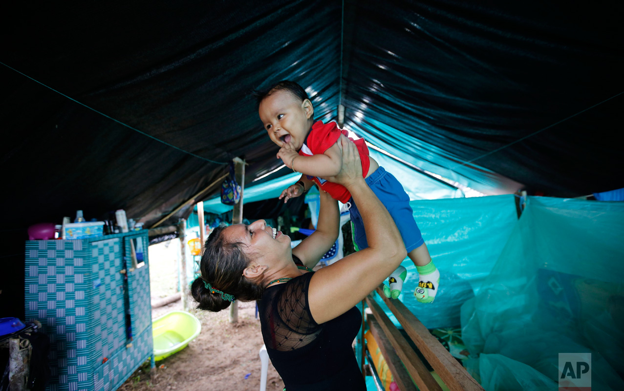 In this Tuesday, Feb. 28, 2017 photo, FARC rebel Jerly Suarez holds up her 9-month-old son Dainer inside her tent at a rebel camp in a demobilization zone in La Carmelita, in Colombia's southwestern Putumayo state. In La Carmelita, where 500 guerrillas are expected to turn over their weapons by June 1, women speak of both the arduous conditions in which they have begun their new lives as mothers and their hopes for raising children in a time of peace. (AP Photo/Fernando Vergara)