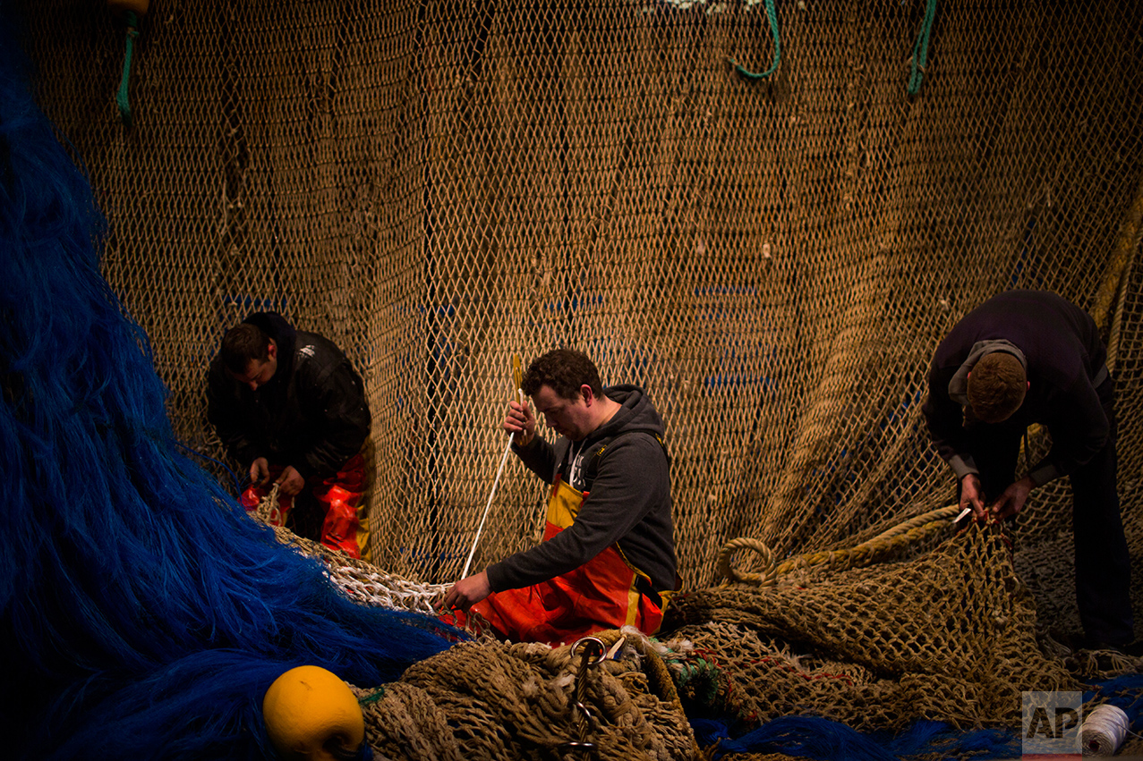 In this Friday, March 3, 2017 photo, fishermen of the Maarten-Jacob ship work fixing their fishing net at the port in The Hague, The Netherlands. (AP Photo/Emilio Morenatti)
