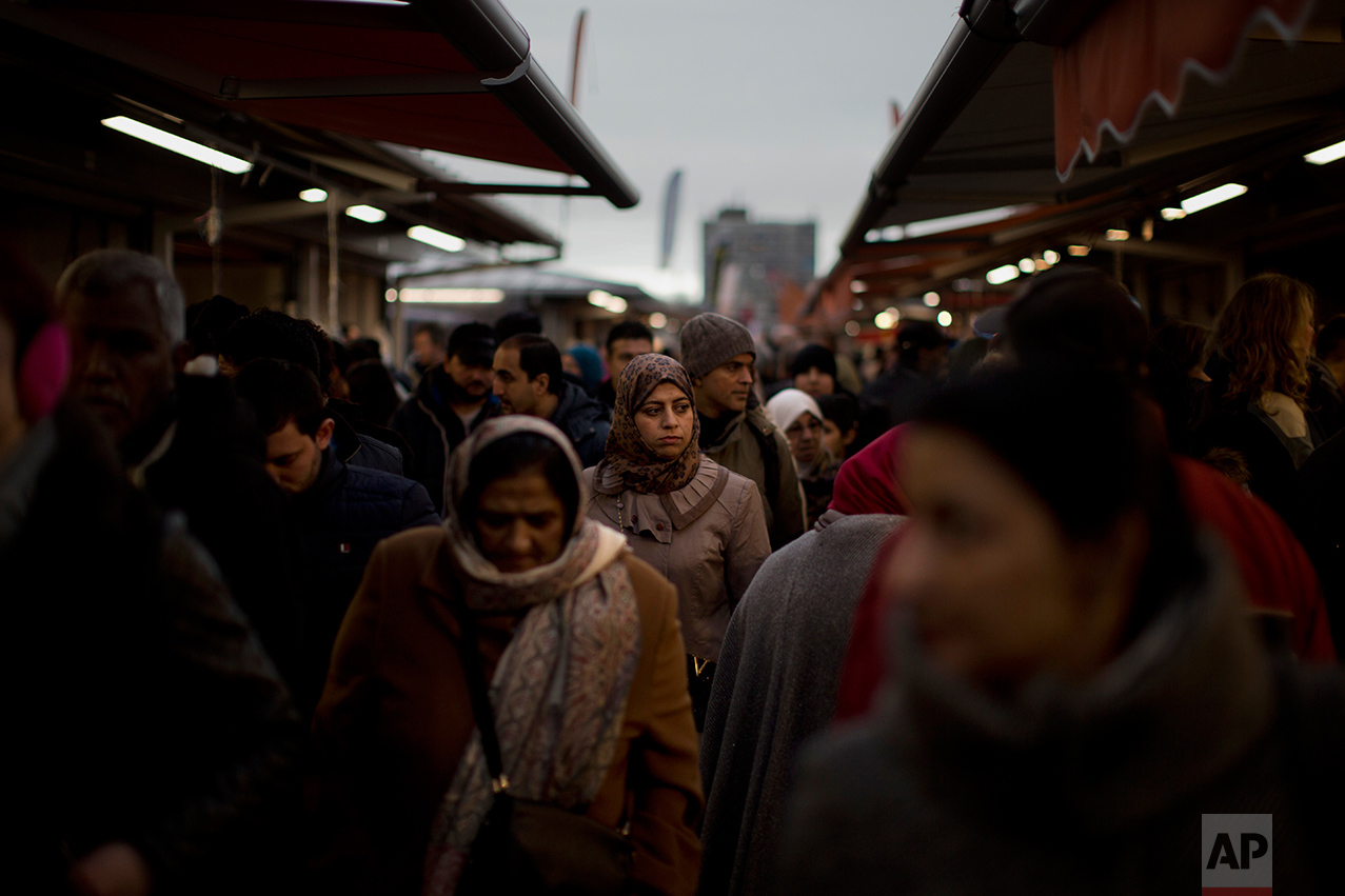 In this Saturday, March 4, 2017 photo, people walk along street stalls at a fruit market in The Hague, The Netherlands. In The Hague's most culturally diverse neighbourhoods, many women wear Muslim headscarves. In the market, young Muslim women eating battered fried fish, a Dutch favourite, took dainty, careful bites to avoid splashing grease on their hijabs. (AP Photo/Emilio Morenatti)