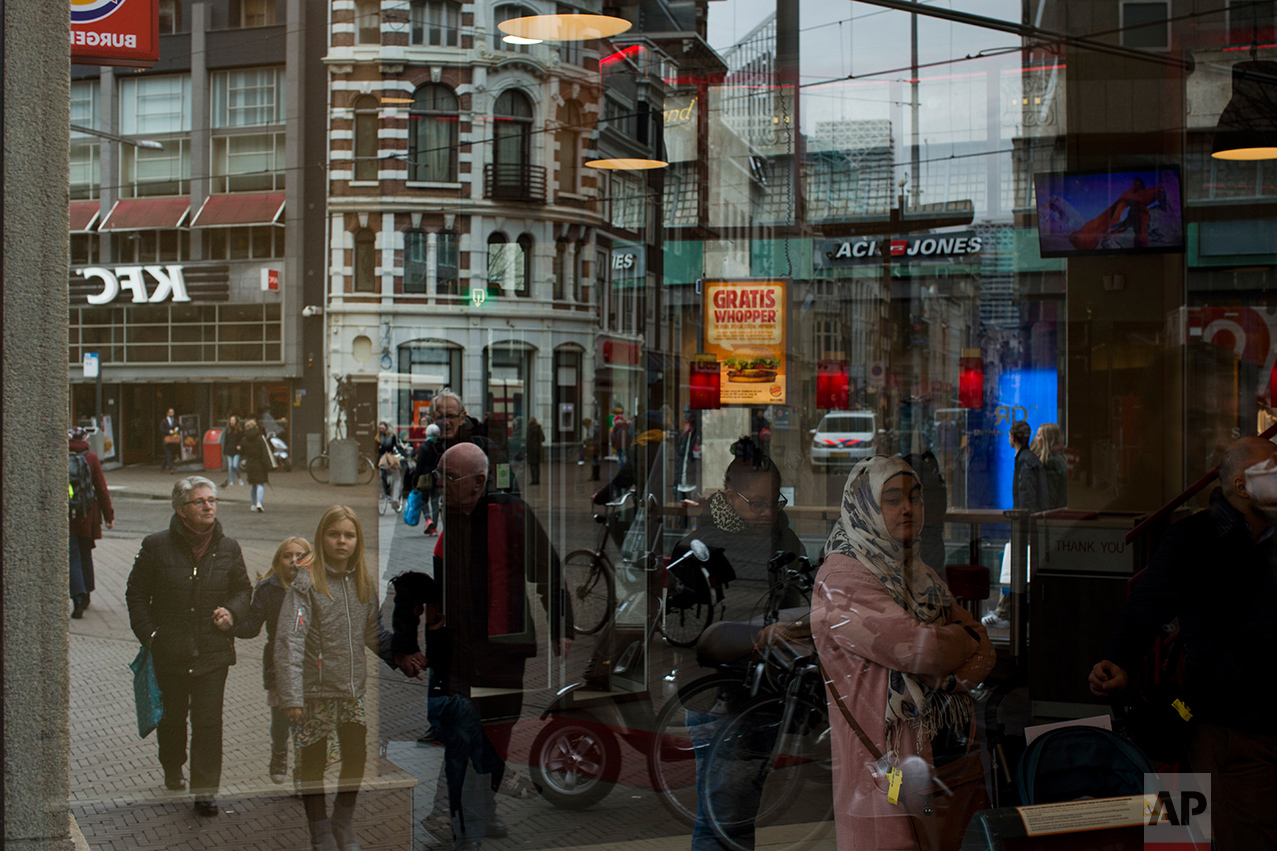 In this Friday, March 3, 2017 photo, people are seen reflected in a restaurant window in The Hague, the Netherlands. Of The Netherlands' 17 million people, just over one in five now have a migrant background _ rising to roughly half-and-half in The Netherlands' four largest melting-pot cities: Amsterdam, Rotterdam, Utrecht and The Hague. (AP Photo/Emilio Morenatti)