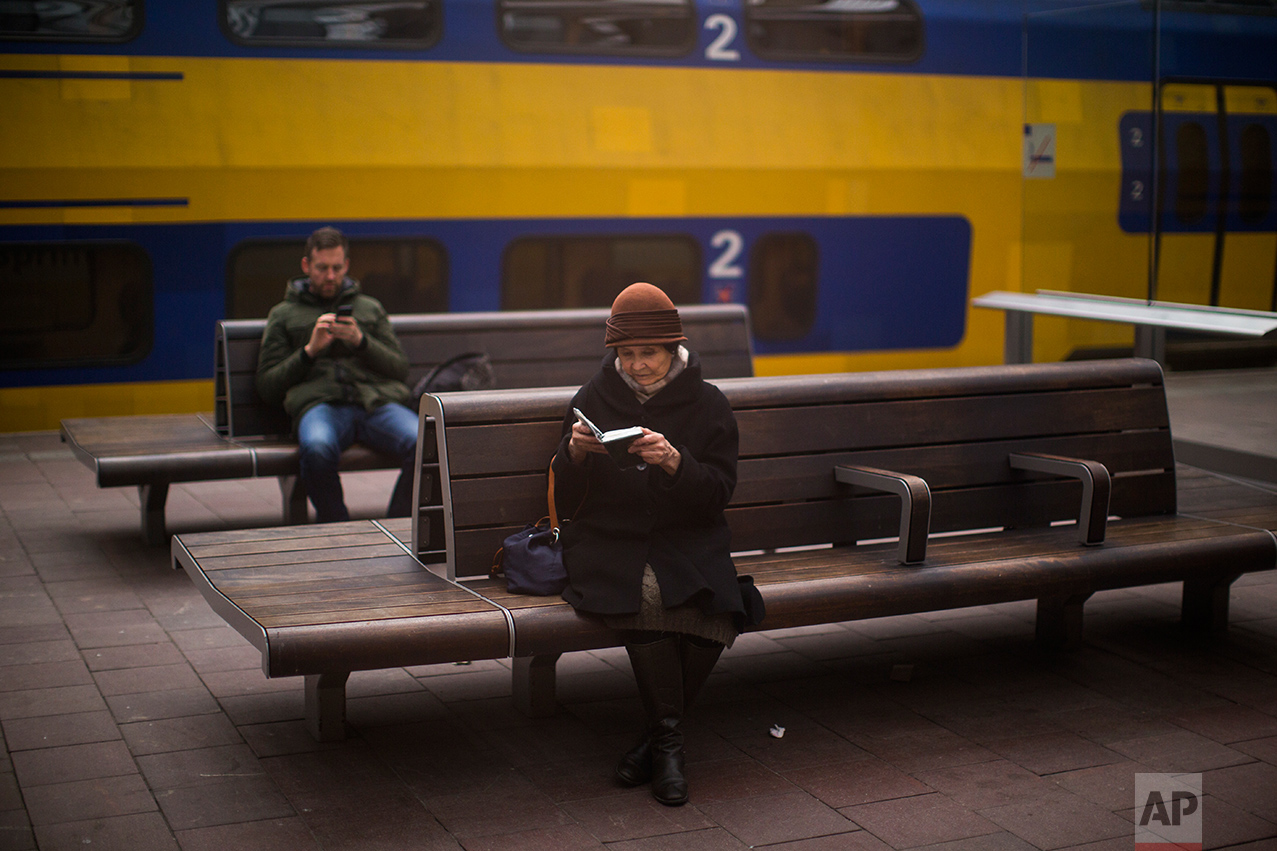 In this Thursday, March 2, 2017 photo, a woman reads the bible at the central station in The Hague, Netherlands. (AP Photo/Emilio Morenatti)