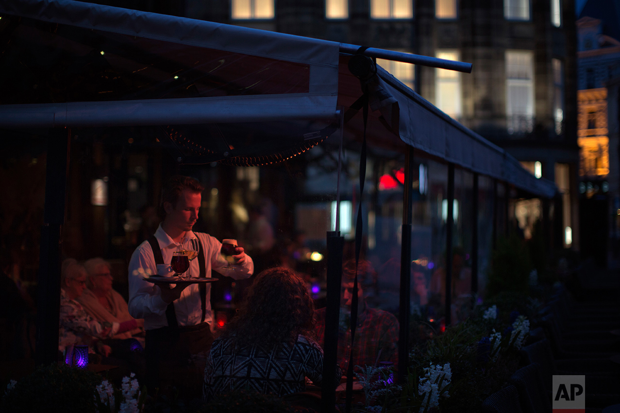 In this Saturday, March 4, 2017 photo, people have dinner at a restaurant at The Hague, The Netherlands. The Netherlands is densely populated, with some of its land reclaimed from the sea. Geert Wilders supporters cite lack of space as another reason for the Netherlands to close its doors. The country is full, they argue. (AP Photo/Emilio Morenatti)