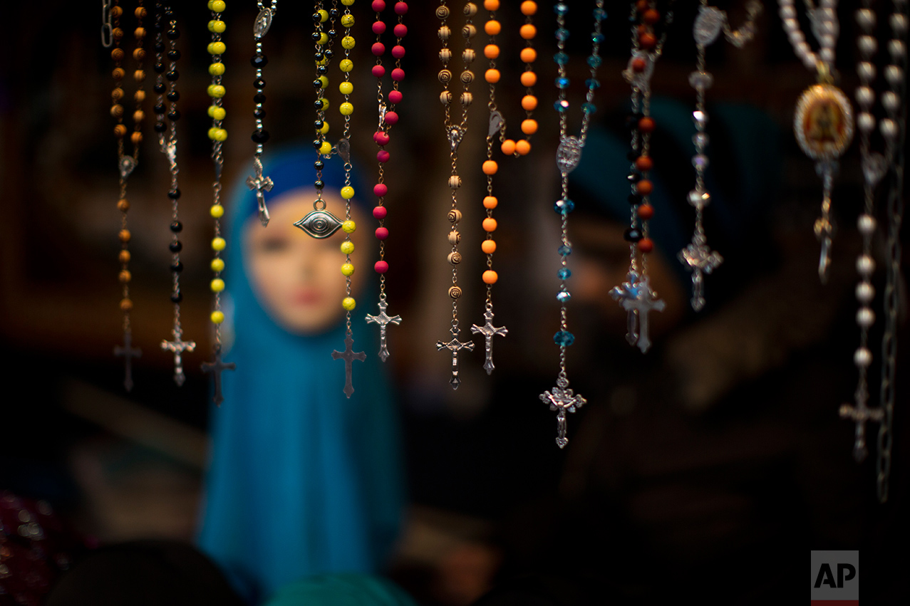 In this Saturday, March 4, 2017 photo, rosary beads are displayed for selling next to a mannequin wearing a headscarf in a market stall at The Hague, The Netherlands. In The Hague's most culturally diverse neighbourhoods, many women wear Muslim headscarves. (AP Photo/Emilio Morenatti)