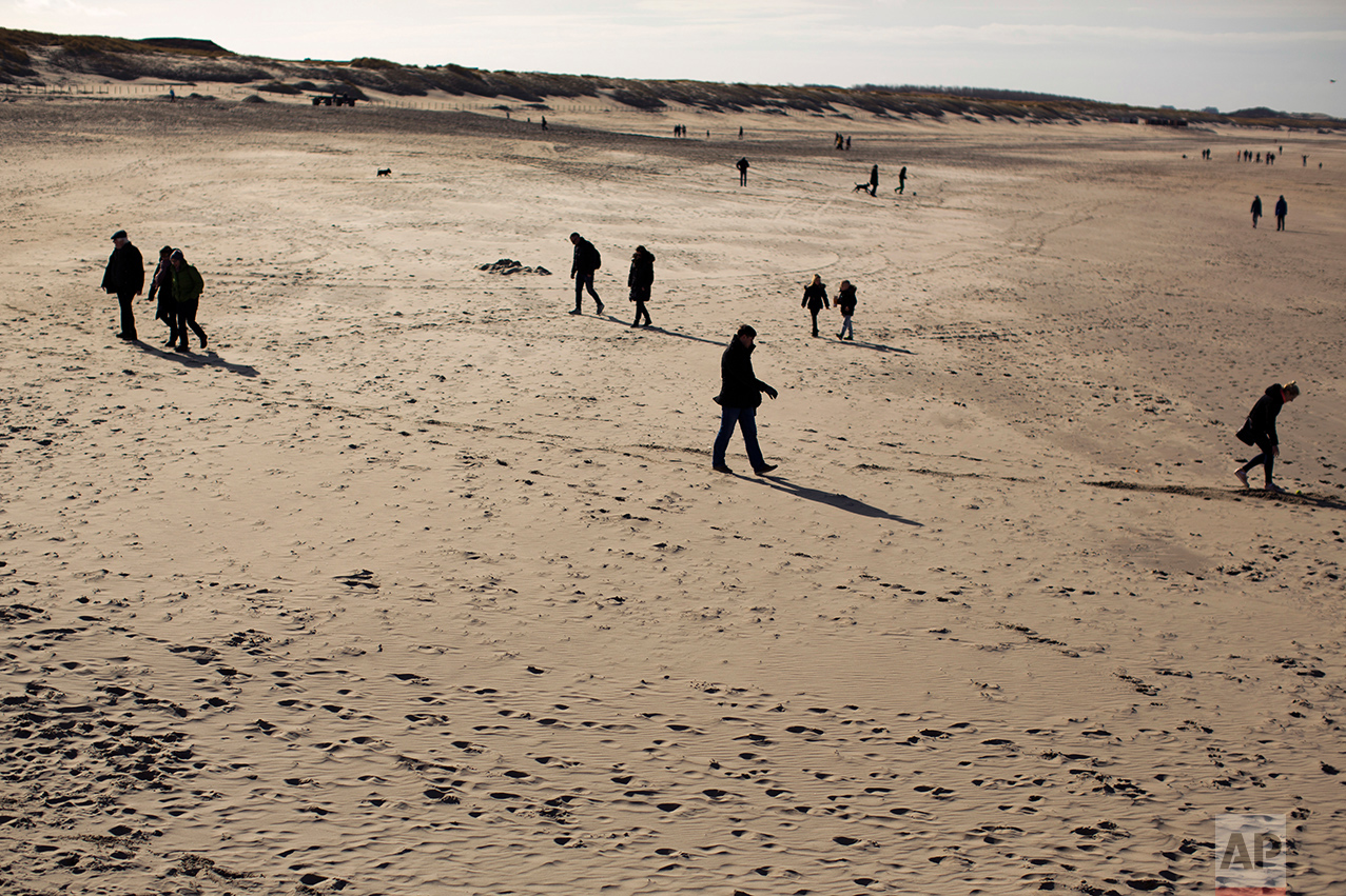 In this Sunday, March 5, 2017 photo, people walk along the beach in The Hague, The Netherlands. Of The Netherlands' 17 million people, just over one in five now have a migrant background _ rising to roughly half-and-half in The Netherlands' four largest melting-pot cities: Amsterdam, Rotterdam, Utrecht and The Hague. (AP Photo/Emilio Morenatti)