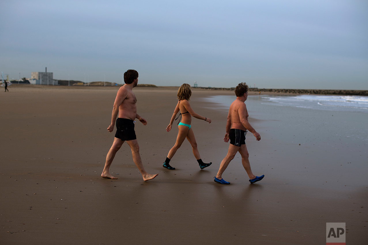 """In this Friday, March 3, 2017 photo, Denice Spans, 30, center, walks next to her father Fred, 62, right, and their friend Rogier, left, as they go for a swim in the sea of The Hague, The Netherlands. """"I think 80 percent of people who vote Wilders are afraid of change,"""" says Denice Spans, a 30-year-old educator who works with asylum seekers. Those voters include her father, Fred, a hairdresser. The two of them swim together in the North Sea in the mornings but don't see eye-to-eye politically. (AP Photo/Emilio Morenatti)"""