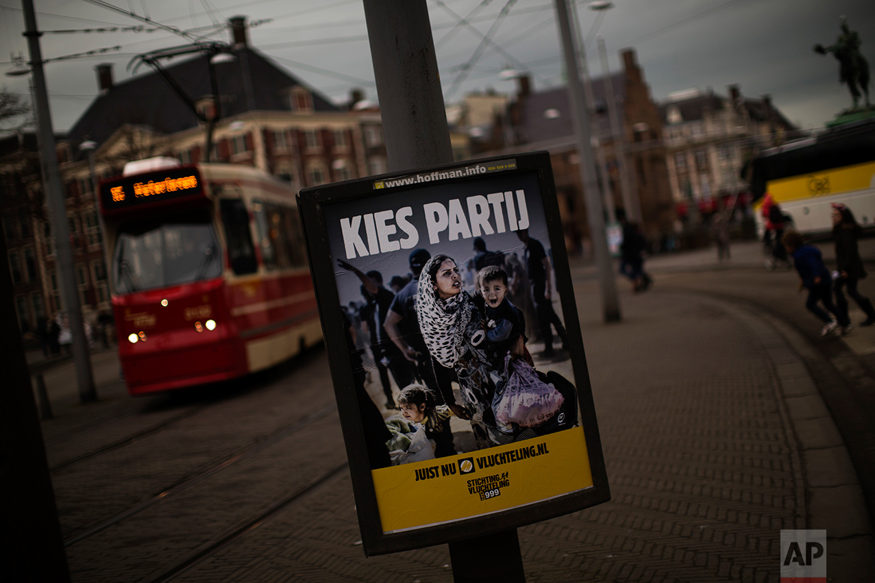 """In this Friday, March 3, 2017 photo, a banner by Stichting Vluchteling (Refugee Foundation of Netherlands), that reads in Dutch """"Choose a Party"""" hangs on a lamppost in The Hague, The Netherlands. Ahead of a Dutch vote that will indicate whether populism in Europe is gathering strength or blowing over, divisive questions about immigration and Islam are testing the Netherlands' famed capacity for tolerance and inclusiveness. (AP Photo/Emilio Morenatti)"""
