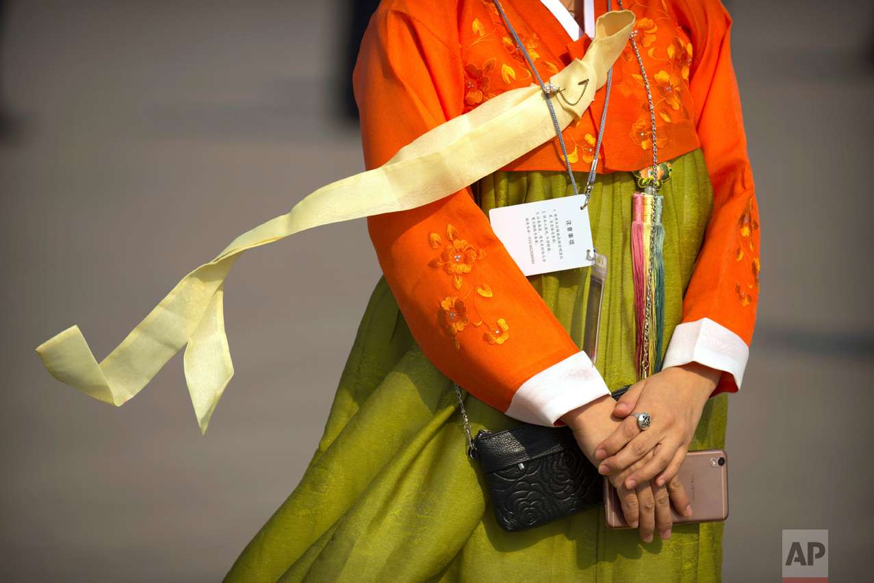 In this Friday, March 3, 2017 photo, a ribbon on a staff member's outfit blows in the breeze as she arrives for the opening session of the Chinese People's Political Consultative Congress (CPPCC) at the Great Hall of the People in Beijing.(AP Photo/Mark Schiefelbein)