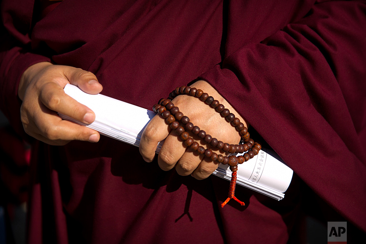 In this Wednesday, March 8, 2017 photo, a Tibetan delegate wears prayer beads and carries rolled-up paperwork as he arrives for a plenary session of China's National People's Congress (NPC) at the Great Hall of the People in Beijing. (AP Photo/Mark Schiefelbein)
