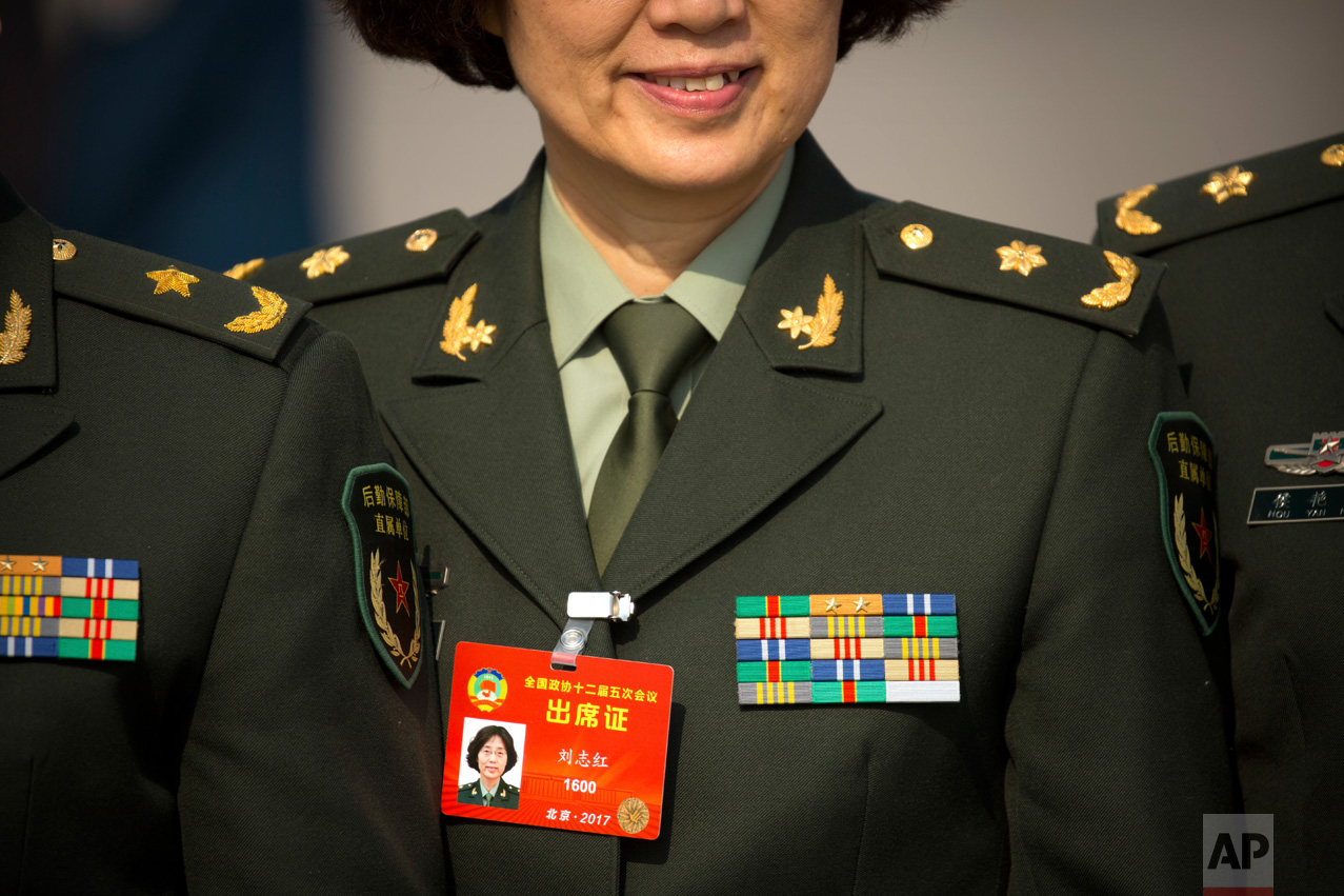 In this Friday, March 3, 2017 photo, a military delegate poses for a group photo as she arrives for of the opening session of the Chinese People's Political Consultative Congress (CPPCC) at the Great Hall of the People in Beijing. (AP Photo/Mark Schiefelbein)