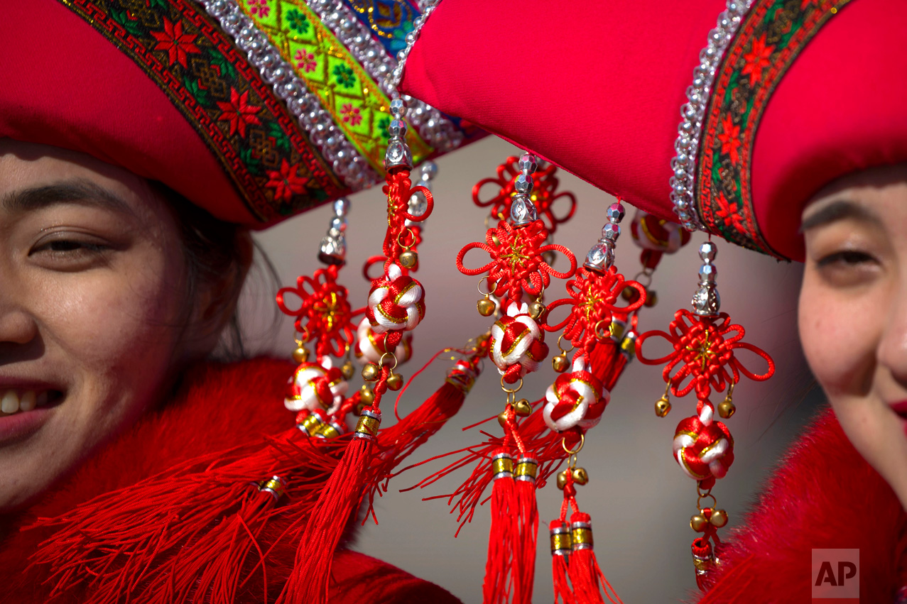 In this Sunday, March 12, 2017 photo, decorations hang from the hats of hospitality staff members as they pose for a group photo during a plenary session of the National People's Congress (NPC) in Beijing. (AP Photo/Mark Schiefelbein)