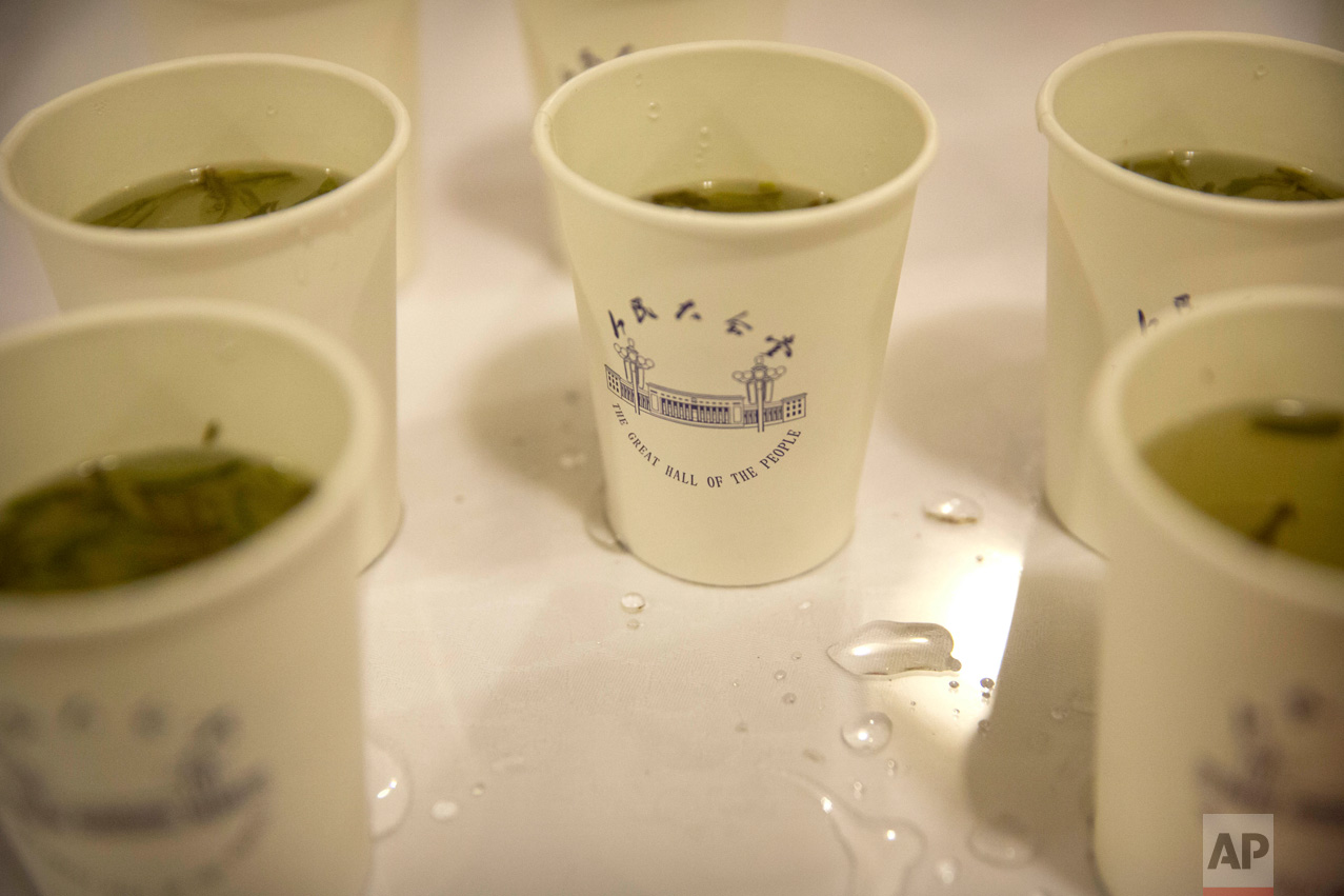 In this Friday, March 10, 2017 photo, cups of green tea bearing an image of the Great Hall of the People are available for delegates and visitors during a plenary session of the Chinese People's Political Consultative Congress (CPPCC) in Beijing. (AP Photo/Mark Schiefelbein)
