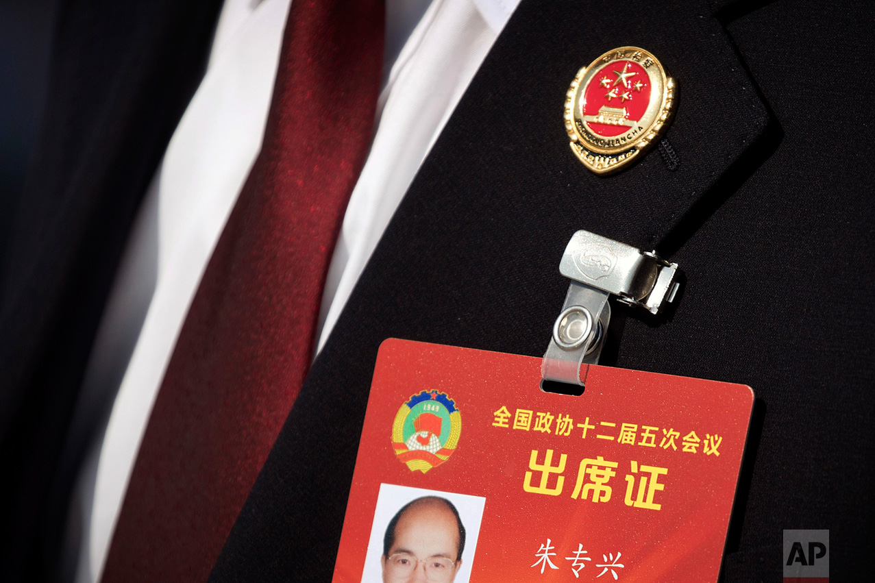 In this Friday, March 10, 2017 photo, a member of China's procuratorate wears a pin on his lapel as he arrives to hear a report by the head of China's Supreme People's Procuratorate during a plenary session of the Chinese People's Political Consultative Congress (CPPCC) in Beijing. (AP Photo/Mark Schiefelbein)