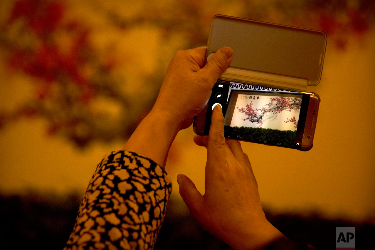 In this Friday, March 10, 2017 photo, a delegate takes a smartphone photo of a painting inside the Great Hall of the People during a plenary session of the Chinese People's Political Consultative Congress (CPPCC) in Beijing. (AP Photo/Mark Schiefelbein)