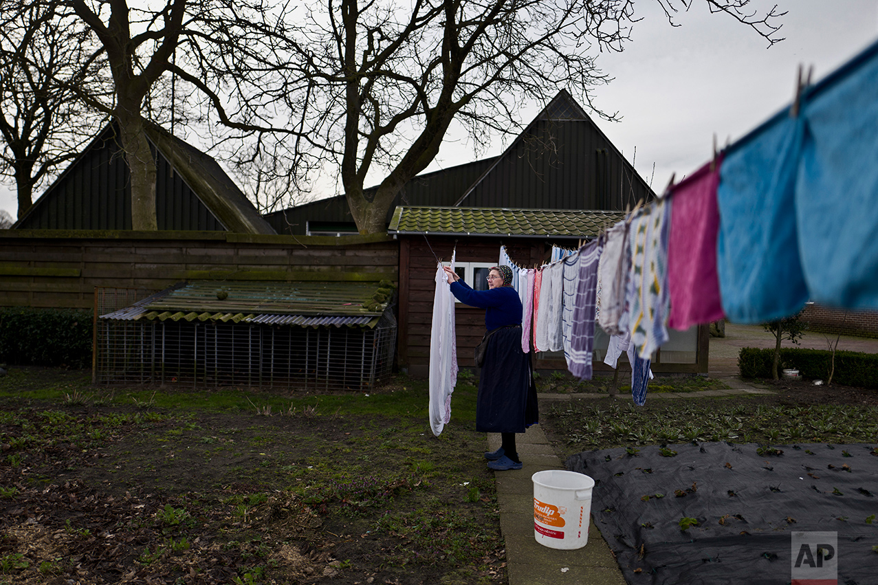 An elderly Dutch woman hangs her laundry in front of her home in Staphorst, Netherlands, Wednesday, March 15, 2017. (AP Photo/Muhammed Muheisen)