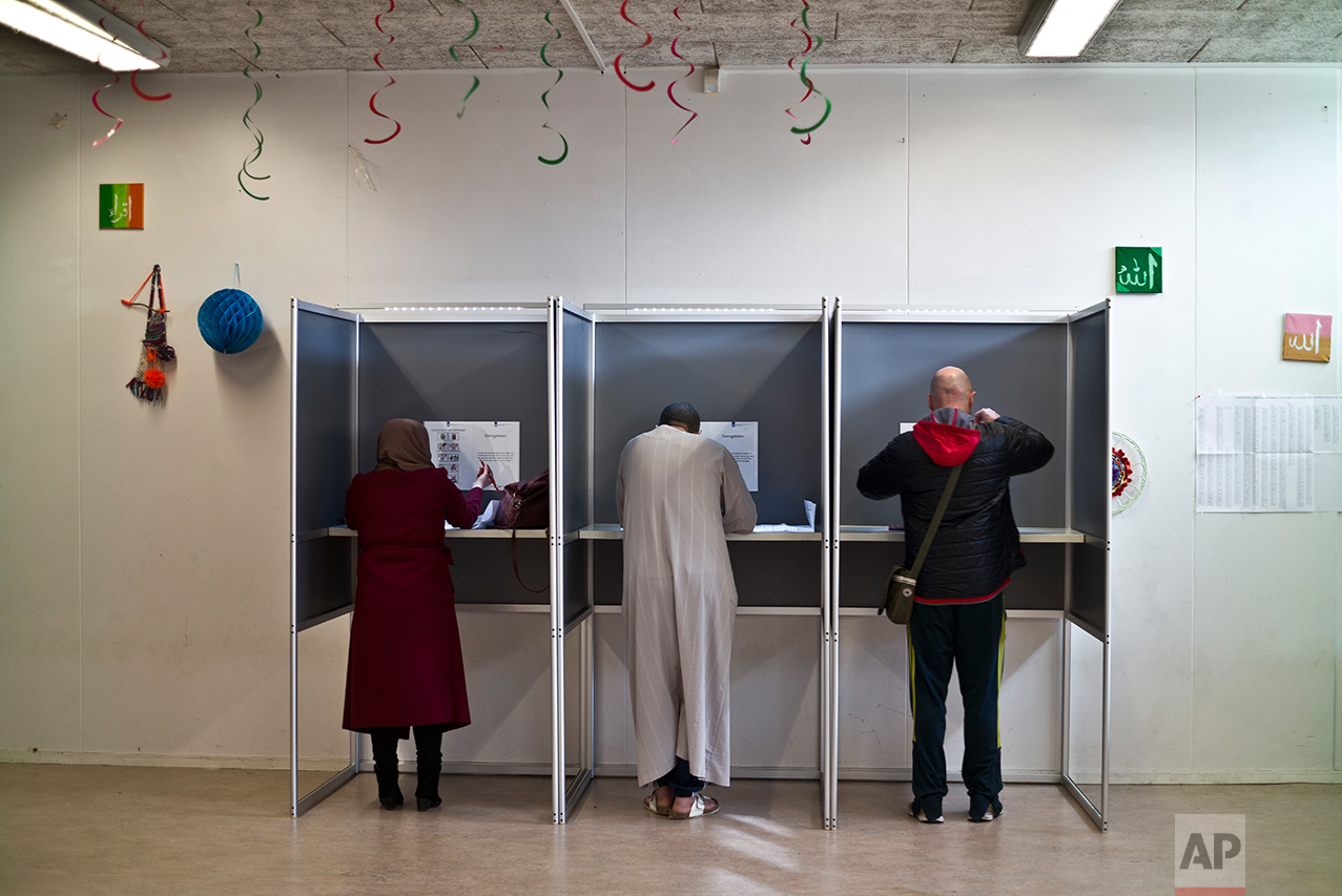 People fill out ballots prior to casting their votes for the Dutch general elections at a polling station set up in a school in Amsterdam, Netherlands, Wednesday, March 15, 2017. (AP Photo/Muhammed Muheisen)