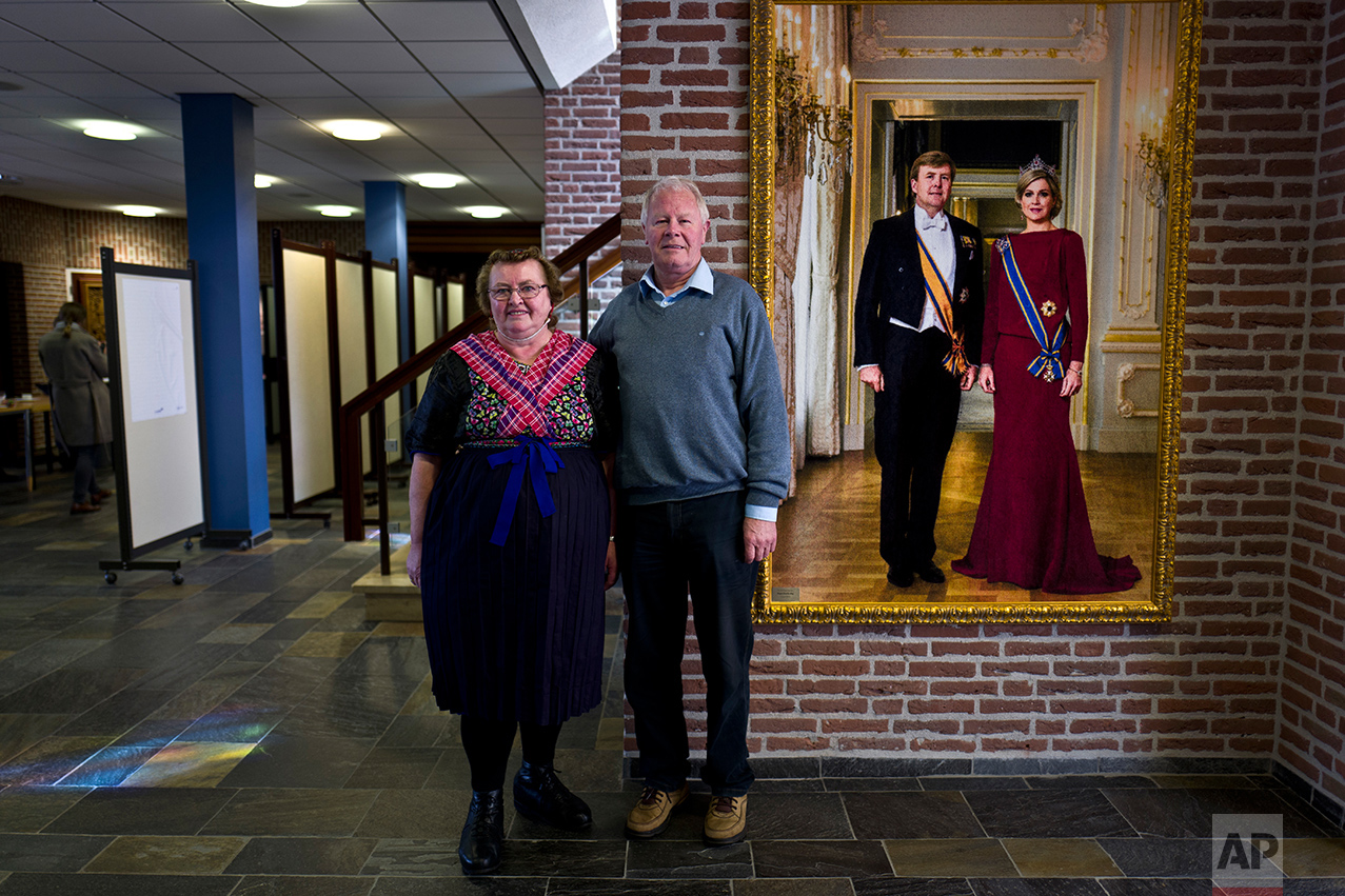 Klaas de Haan, 69, right and his wife Aaltje, 67, left, of Netherlands pose for a picture after casting their ballots for the Dutch general elections inside a polling station set up in the city hall in Staphorst, Netherlands, Wednesday, March 15, 2017. (AP Photo/Muhammed Muheisen)