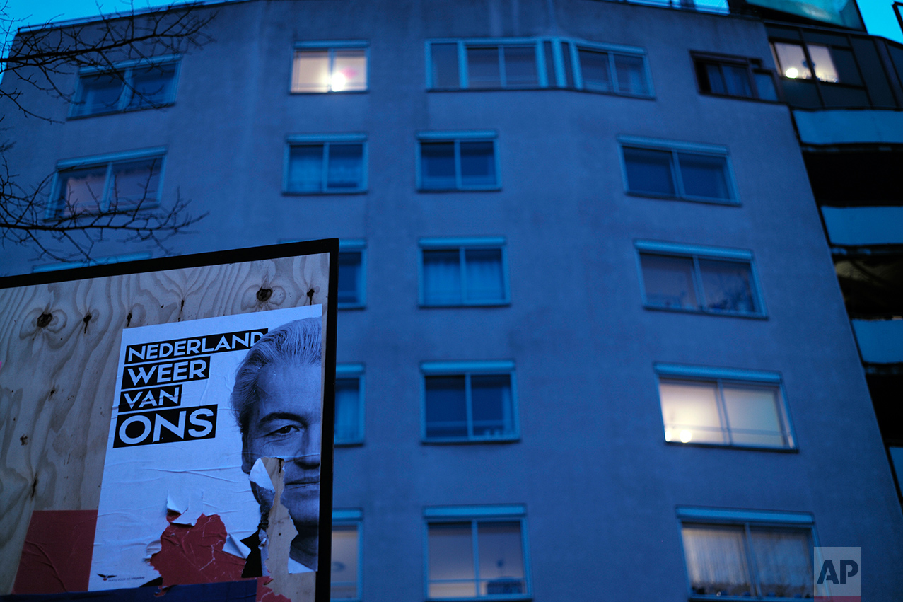 A damaged election poster showing firebrand anti-Islam lawmaker Geert Wilders, is displayed on a billboard in Amsterdam, Netherlands, Monday, March 13, 2017. (AP Photo/Muhammed Muheisen)