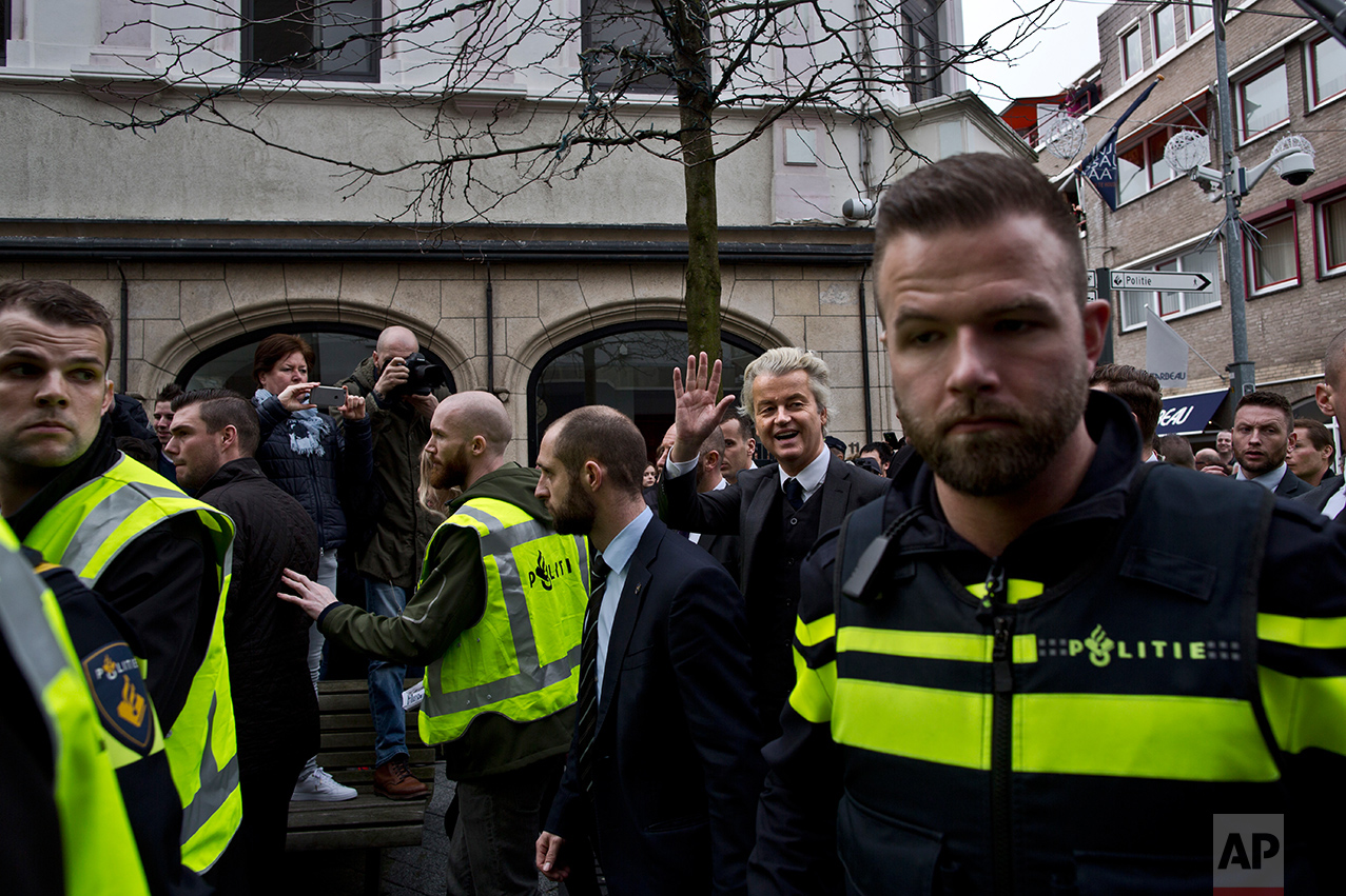 "Firebrand anti-Islam lawmaker Geert Wilders, second right, surrounded by police officers and security guards as he waves to supporters during a campaign stop in Heerlen, Netherlands, Saturday, March 11, 2017. Wilders' party is campaigned under the slogan ""The Netherlands, Ours Again"". (AP Photo/Muhammed Muheisen)"
