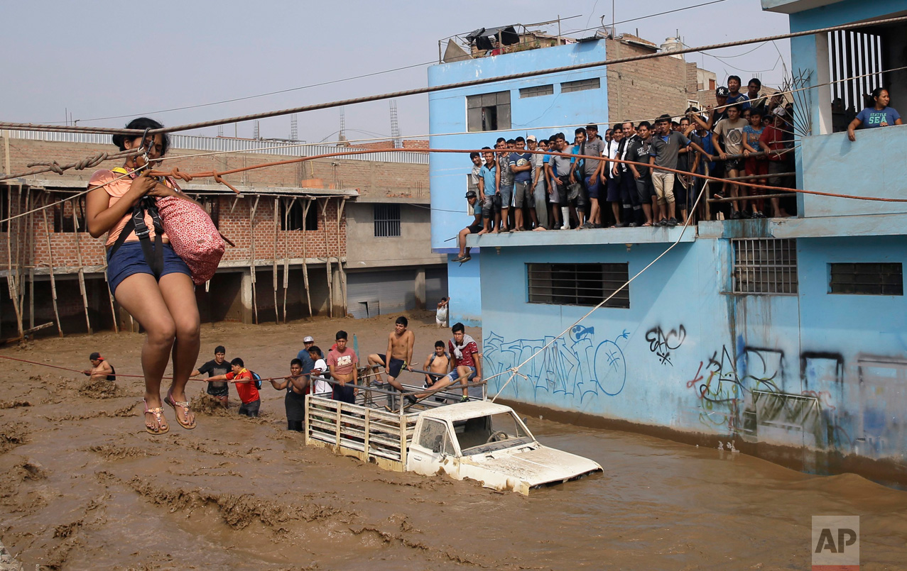 A woman is pulled to safety in a zip line harness in Lima, Peru, on Friday, March 17, 2017. Intense rains and mudslides over the previous few days have wrought havoc around the Andean nation and caught residents in Lima, a desert city of 10 million where it almost never rains, by surprise. (AP Photo/Martin Mejia)