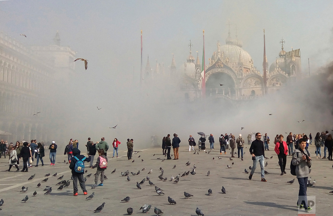 Smoke rises in St. Mark's Square in Venice, Italy, Friday, March 17, 2017. News reports said thieves attempting to rob a jewelry store in the landmark area set off panic among tourists when they ignited smoke bombs to cover their movements. (Andrea Venturini via AP)