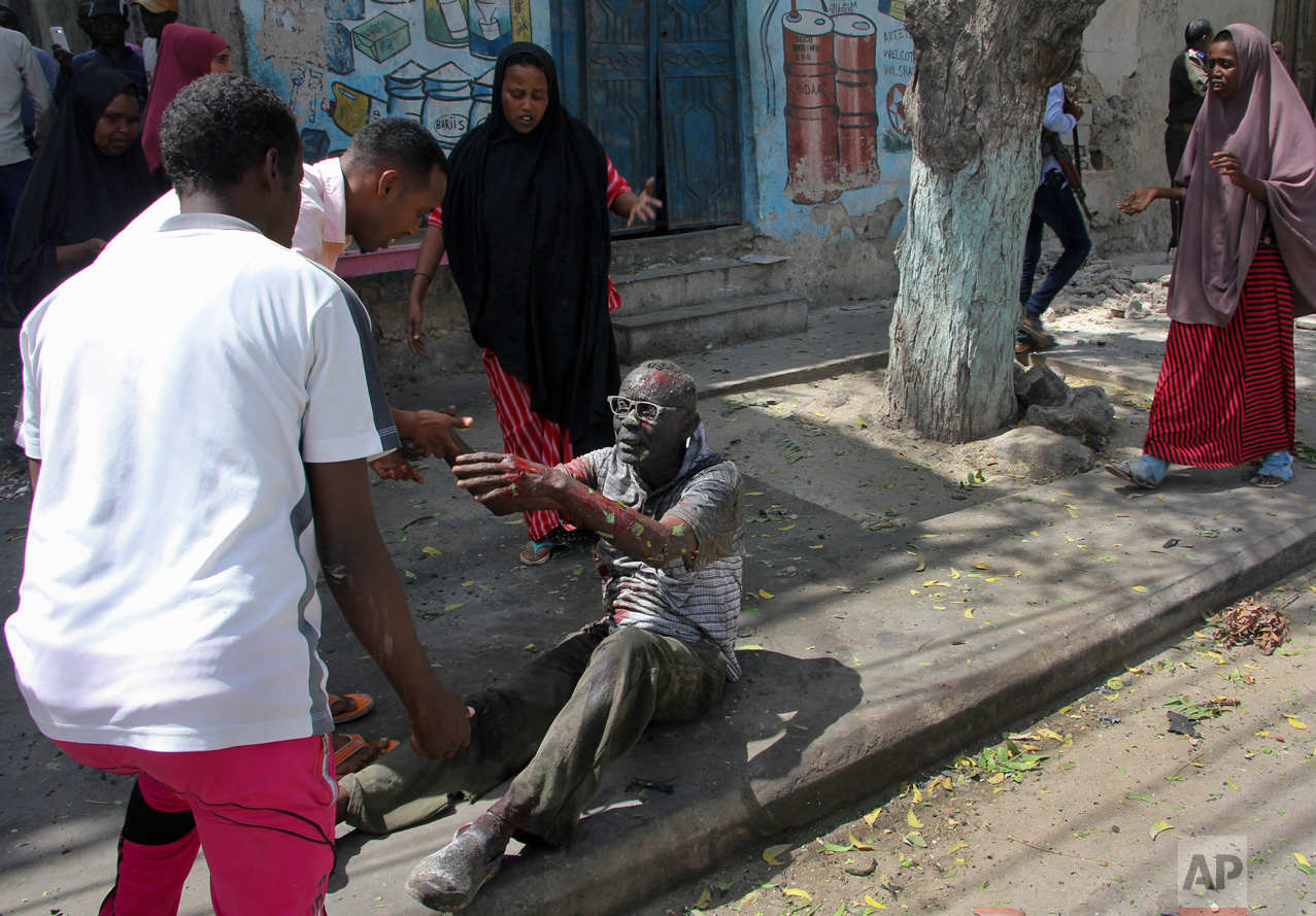 A wounded man reaches out to rescuers after a car bomb attack in Mogadishu, Somalia, on Monday, March 13, 2017. A suicide car bomber detonated explosives near the Weheliye hotel in the capital Monday morning, killing several on the busy Maka Almukarramah road, according to police. (AP Photo/Farah Abdi Warsameh)