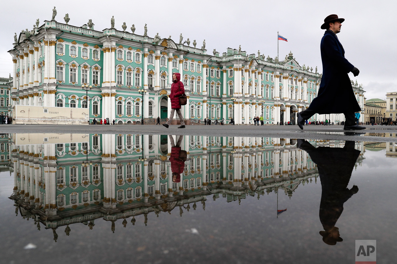 People walk past the Zimny (Winter) Palace at Dvortsovaya Square in St. Petersburg, Russia on Saturday, March 11, 2017. A century after the days that shook the world, the anniversary of the 1917 revolution in Russia is being marked with little official fanfare from the Kremlin. It once was celebrated with pomp and parades but now no longer fits the narrative of political and religious leaders. (AP Photo/Dmitri Lovetsky)